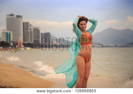 Brunette Girl In Bikini Transparent Frock Stands Tip-toe On Sand
