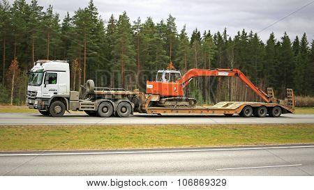 White Mercedes-Benz Truck Hauls Hitachi Excavator On Motorway
