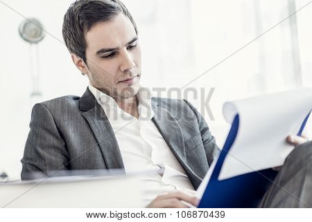 Confident Young Businessman Sitting At His Desk Reading A Document