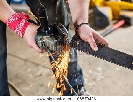 Worker With Angle Grinder For Metal On Workplace