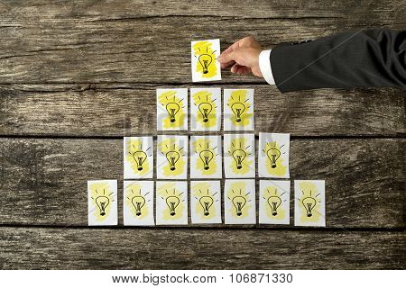 Male Hand Placing White Cards With Yellow Light Bulbs In A Form Of A Pyramid