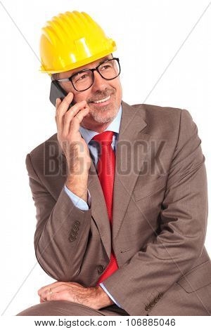 side view of a smiling old construcion engineer talking on the phone and looks away from the camera