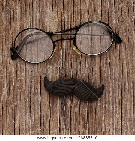 a pair of round-framed eyeglasses and a fake mustache on a rustic wooden surface, depicting a man face