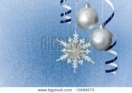 Silver Christmas baubles snowflake and ribbon ornament on blue background of defocused lights. Shallow DOF. poster