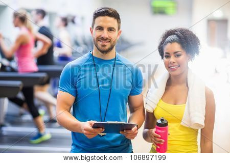 Trainer and client smiling at camera at the gym poster