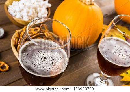 Craft pumpkin beer in beer glasses with salty pretzels and popcorn. poster