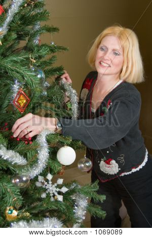 beautiful blonde woman decorating a christmas tree. poster