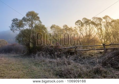 Wooden Fence In Fog On Frozen Meadow At Sunrize