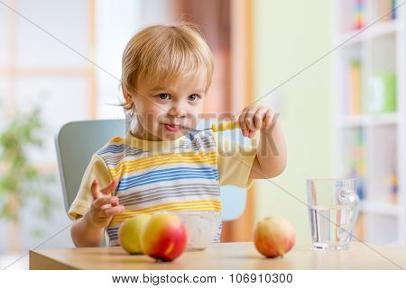 Happy child eating food cheese with fruits at home