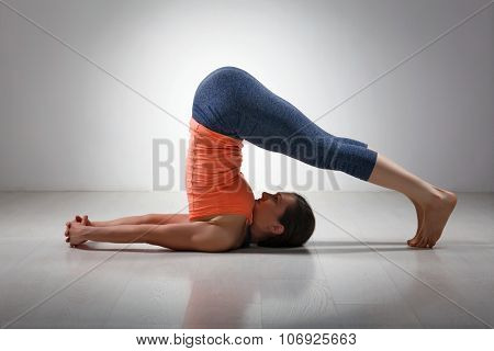 Beautiful sporty fit yogini woman practices yoga asana Halasana - plow pose