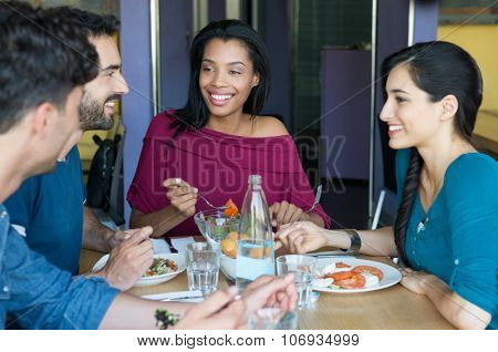 Closeup shot of young women and men having meal. Friends looking at eachother during the lunch. Smiling young friends eating together at restaurant in a summer day.