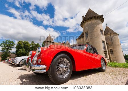 BEAUNE FRANCE - JUNE 12 2010: Red classic Jaguar XK 140 sportscar in front of the Savigny castle.