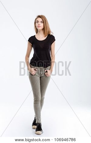 Full length portrait of a casual thoughtful woman looking away isolated on a white background