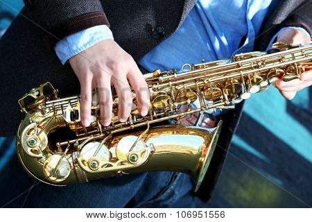 Saxophonist plays jazz on the street, close up