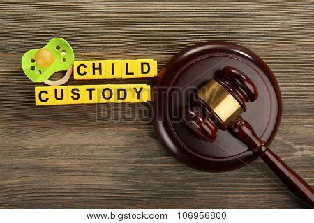 A gavel, a dummy and blocks regarding child-custody and divorce concept poster