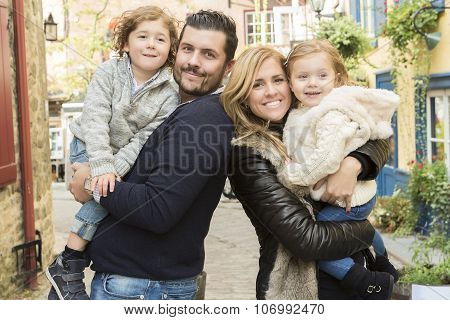 Cheerful young parents holding kids