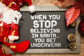 Blackboard with the text: When You Stop Believing In Santa... You Get Underwear in a christmas conceptual image poster