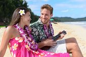 Man on beach playing ukulele instrument on Hawaii with having fun. Young couple, woman and man in love on beach vacations in Hawaiian clothing wearing Aloha shirt dress and flower lei. poster