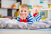 Cute little boy in striped pajamas lies on bed poster