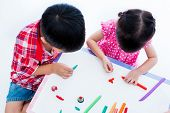 Top view. Little Asian children playing and creating toys from play dough on table on white background. Strengthen the imagination of child poster