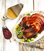 Roasted turkey with bacon and garnished with chestnuts and brussels sprouts. Prepared for Thanksgiving or Christmas dinner. poster