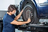 Male mechanic fixing car tire with wrench at repair shop poster