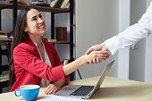 assured businesswoman shaking mans hand and looking he in office poster