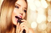 Singing Girl with microphone over golden glowing background. Karaoke party. Beauty model girl singer with a microphone singing and dancing. Disco party. Holiday Celebration poster