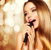Singing Teenage Girl with microphone over golden glowing background. Karaoke party. Beauty teen model girl singer with a microphone singing and dancing. Disco party. Holiday Celebration poster