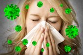 Portrait of a ill blond woman who is sneezing virus in a tissue poster