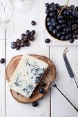 Blue mould, mold cheese with fresh grape on a white wooden background poster