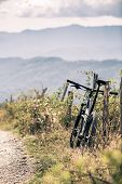 Mountain bike resting on a fance singletrack trail in autumn mountains. Cycling MTB on rural country road or single track. Sport fitness motivation and inspiration in beautiful inspirational landscape. poster