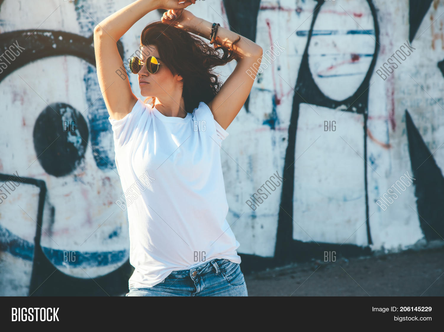 Model wearing plain white tshirt and hipster sunglasses posing against  street wall, teen urban clothing