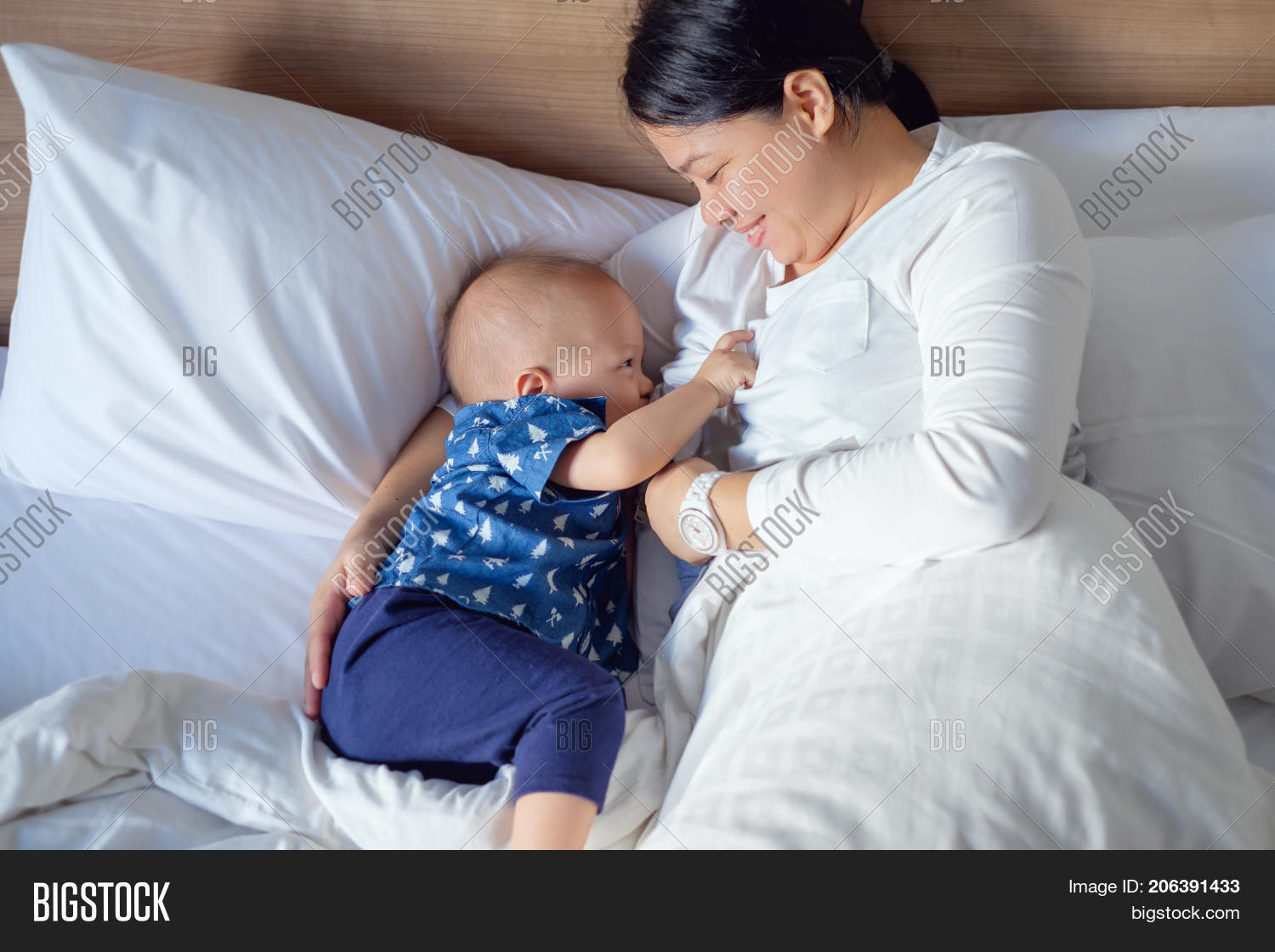 Asian mother is breastfeeding Cute little Asian 14 months / 1 year old  toddler baby boy