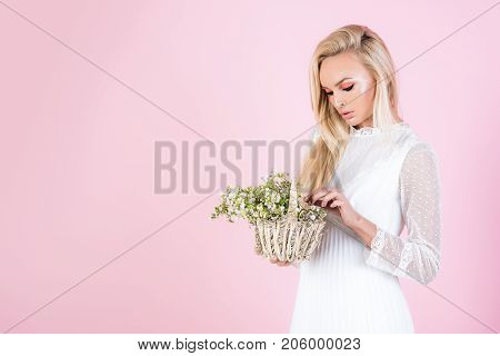 Beautiful girl in a white dress is holding a basket of daisies in her hands. Girl with make-up and flowers. Spring concept youth woman and nature tender girl on a pink background with pink shadows