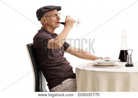 Senior sitting at a restaurant table and drinking red wine isolated on white background
