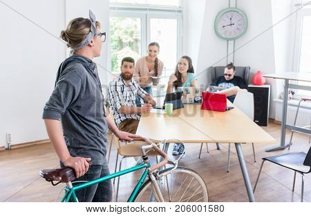 Active young woman holding a commuter bike while talking with her colleagues in the modern office of a shared co-working space for independent workers