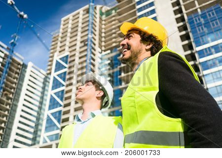 Architects or civil engineers on large construction site giving instructions