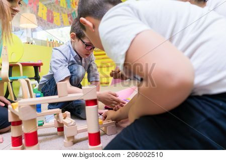 Cute boy wearing eyeglasses while building with attention and patience a wooden structure during an educational group activity at the kindergarten