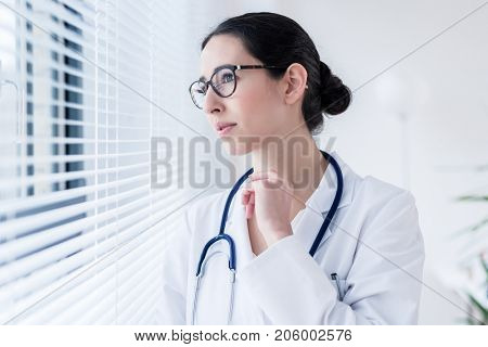 Side view portrait of a young female doctor daydreaming while looking through the window during break in a modern hospital or medical center