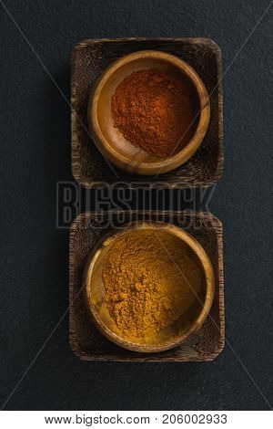 Red chili powder and turmeric powder in a bowl on black
