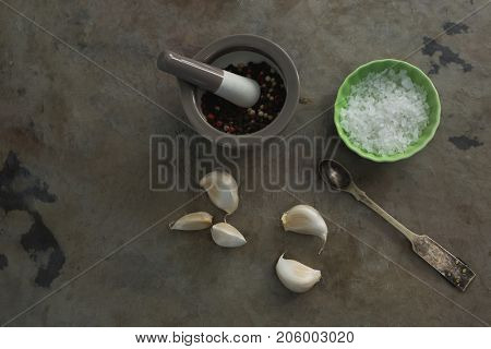 Overhead of black pepper in mortar and pestle with bowl of salt and garlic