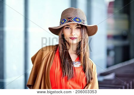 Fashion portrait of young hippie woman model in summer sunny day in bright colorful hipster clothes in hat