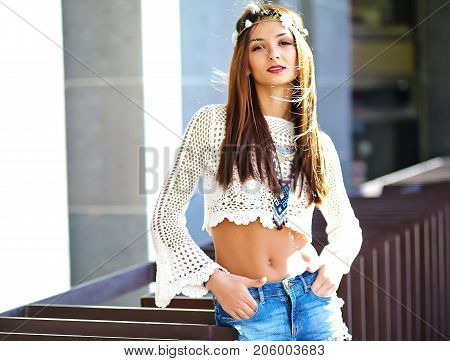 Blurred funny stylish sexy smiling beautiful young hippie woman model in summer white hipster clothes posing in the street