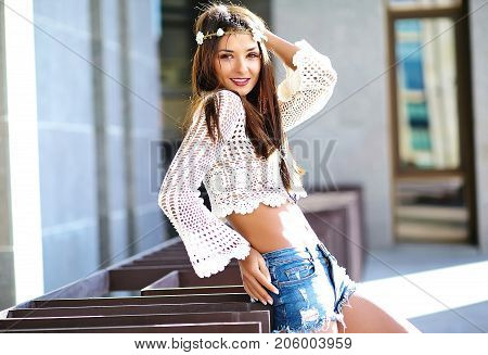 Funny stylish sexy smiling beautiful young hippie woman model in summer white hipster clothes posing in the street