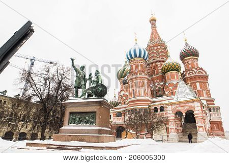 View of Monument Мinin with Pozharsky Vasily Blazhennogo's cathedral surrounding by snow in winter season at Moscow, Perspective of architecture Saint Basil Cathedral with a man in black overcoat standing beside and famous monument covered in snowy