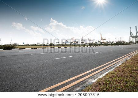 empty asphalt road near commercial dock in blue sky