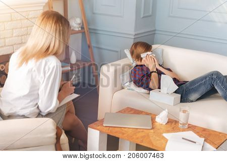 Reveal your emotions. Depressed teenager boy lying on the couch and crying while talking with his psychologist