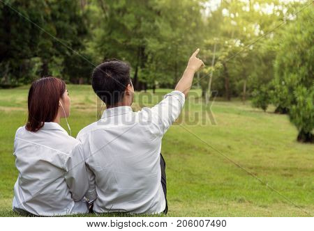 Back side of asian couple sitting and pointing the vision in the park lover and lifestyle concept