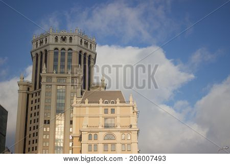 Landscape of pale yellow hexagon tower and small building under blue sky and smooth cloudy background its nice day in Moscow, Pleasant weather in Russia with focus of light yellow structure with windows mirrors all around reflection view and beautiful sky